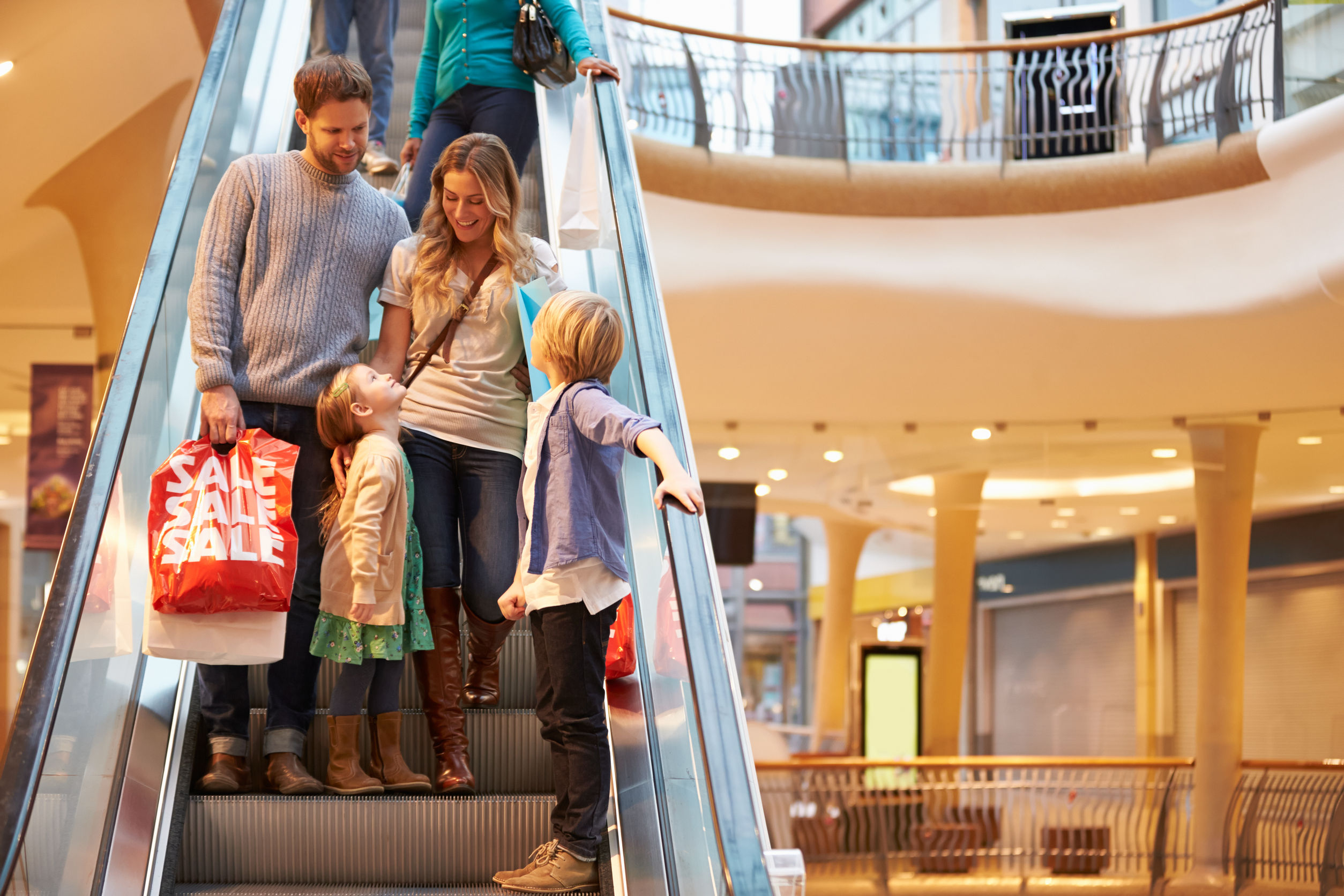 family on escalator in shopping mall together -- shopping experience