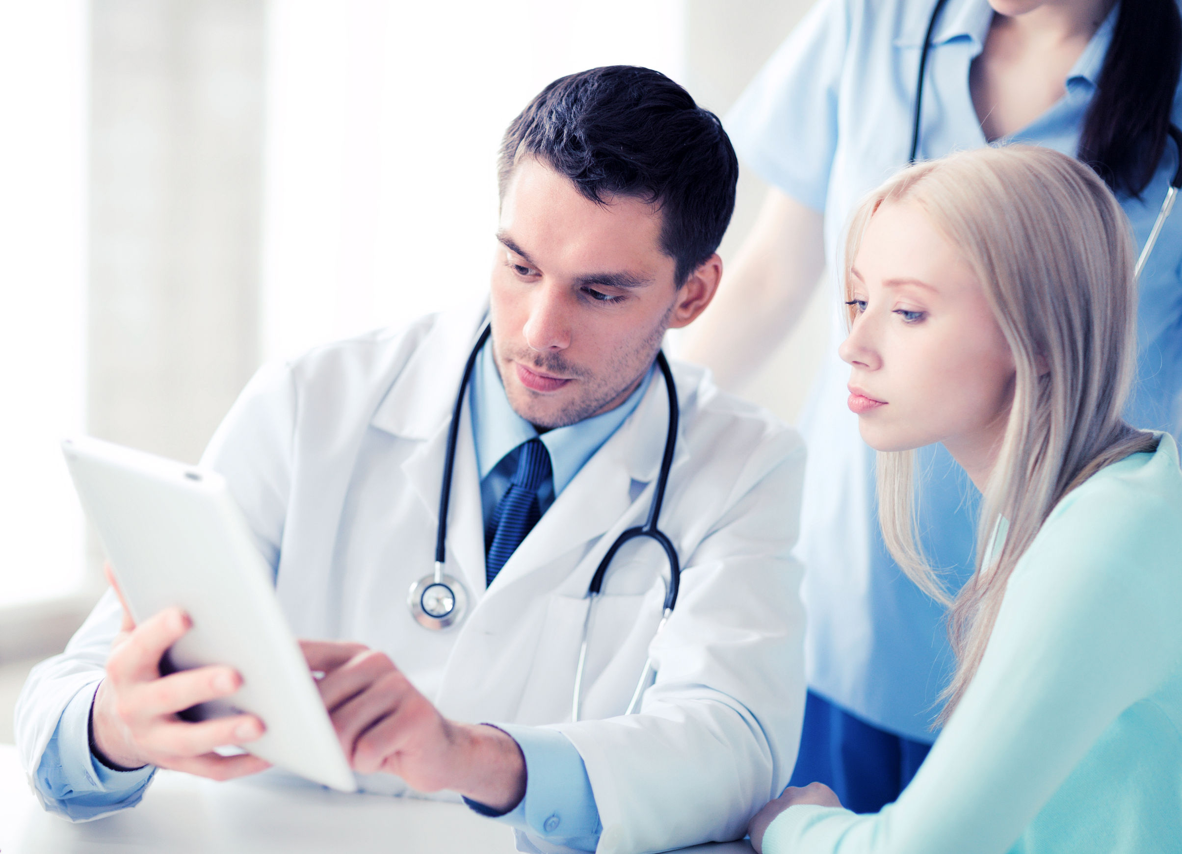 doctor showing something patient on tablet pc in hospital