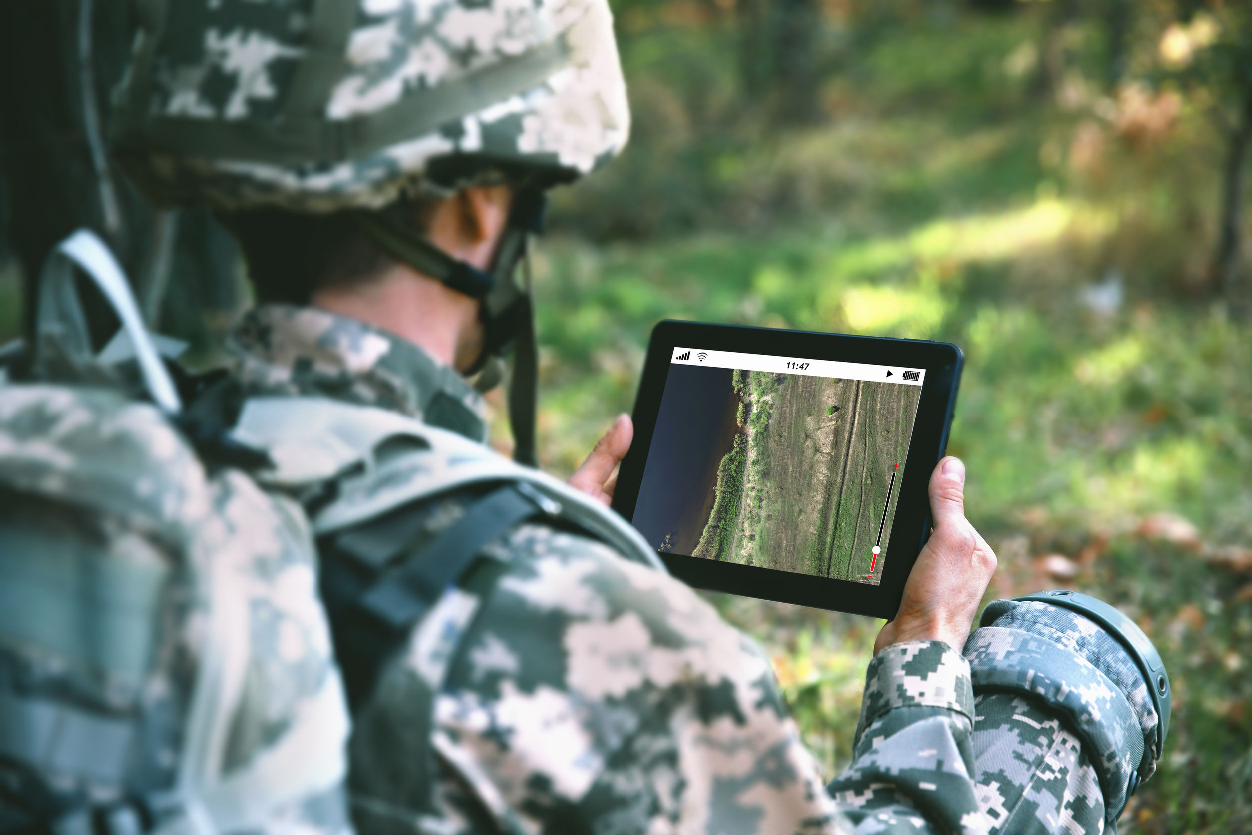 soldier using map on tablet for orientation at forest