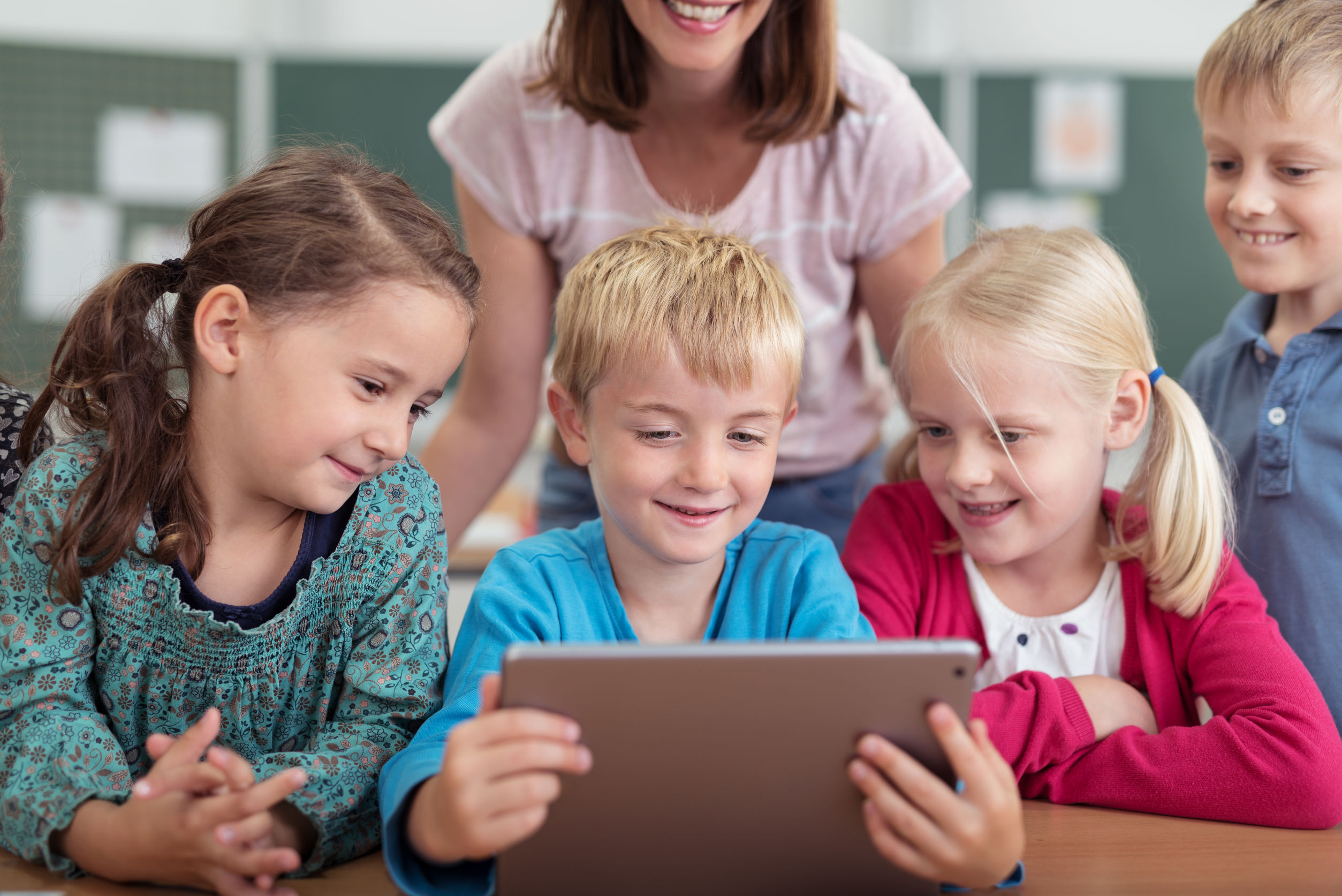 Smiling schoolchildren looking at a tablet - AV in education